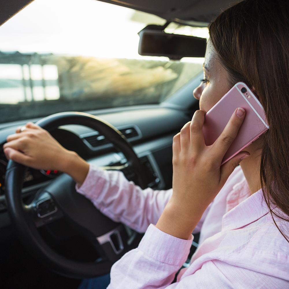 mulher-dirigindo-seu-automóvel-enquanto-fala-no-celular