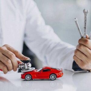 médico-examinando-carro-vermelho-enquanto-segura-ferramentas-para-troca-de-óleo