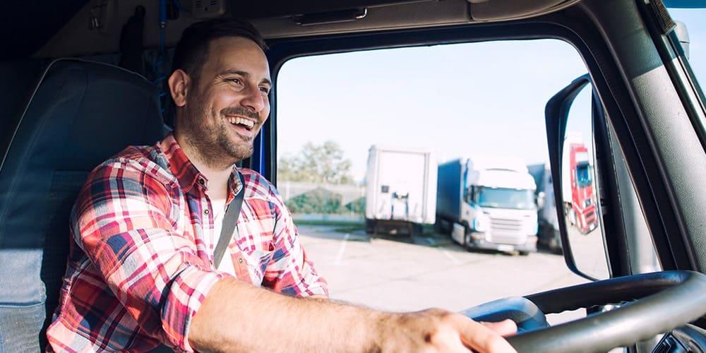 homem-de-camisa-xadrez-dirigindo-seu-caminhão-feliz