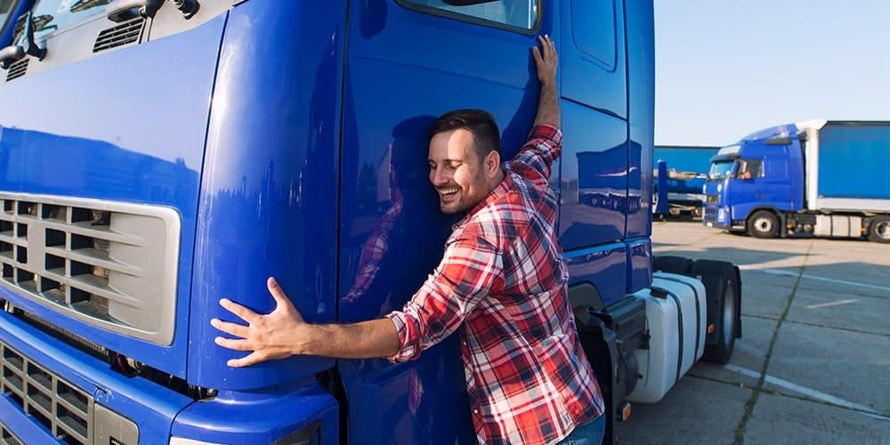 homem-de-camisa-xadrez-abraçando-caminhão-azul