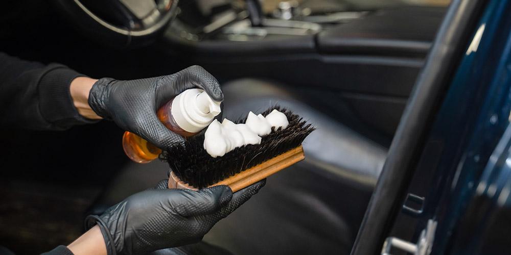 mão-enluvada-segurando-escova-e-produto-de-limpeza-em-espuma-para-limpar-o-veículo-e-evitar-mofo-no-carro
