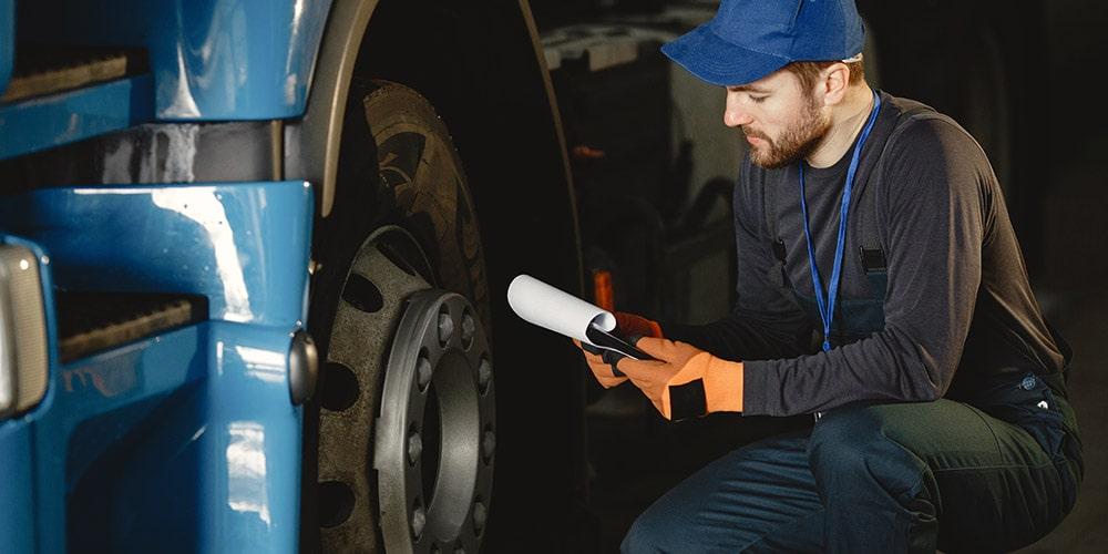 mecânico-de-boné-azul-agachado-ao-lado-de-pneu-de-caminhão