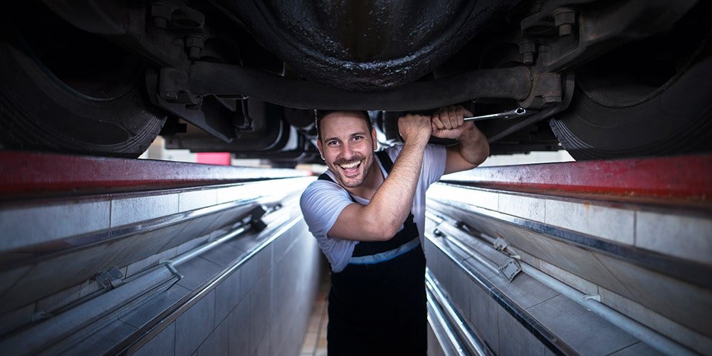 homem-realizando-manutenção-em-baixo-de-caminhão