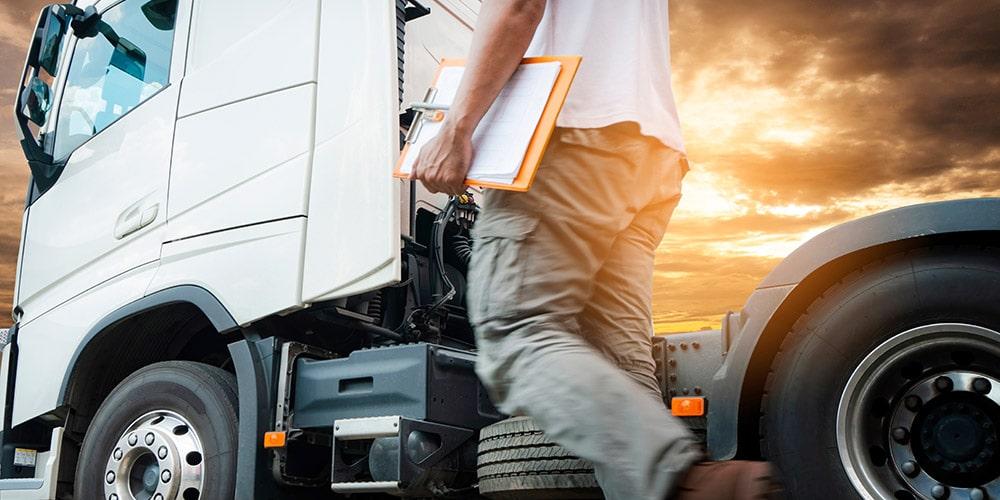 homem-segurando-prancheta-caminhando-em-direção-a-caminhão