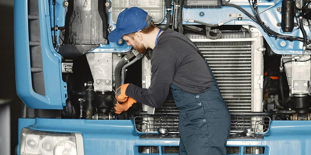 mecânico-realizando-manutenção-em-frente-de-caminhão-azul